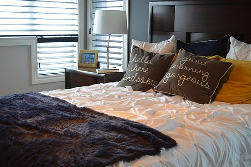 Cama de tonalidades oscuras con sábanas blancas, y cojines marrones con bordados.